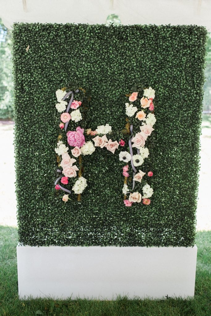 greenery wall with floral accents at bridal shower