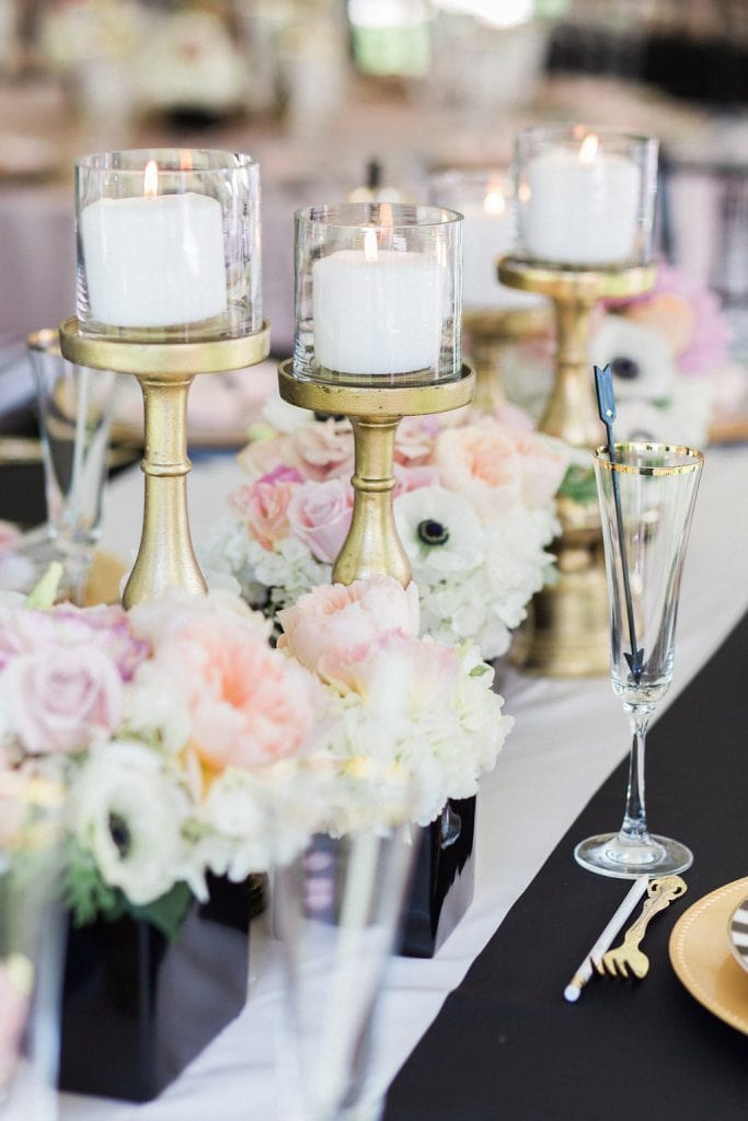 gold candle holders on black and white table cloth with pink and white flowers