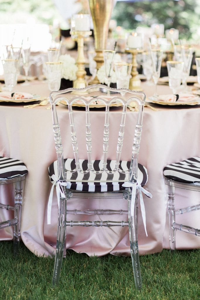 acrylic chairs with black and white cushions and pink table cloth