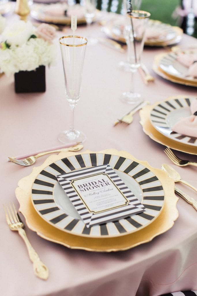 black and white plate with gold charger and pink table cloth