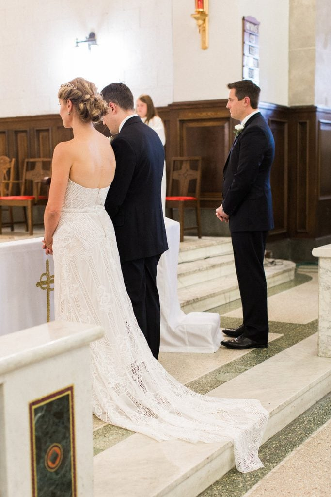 Bride and groom at the alter during their wedding ceremony at St. Anselm Catholic Church