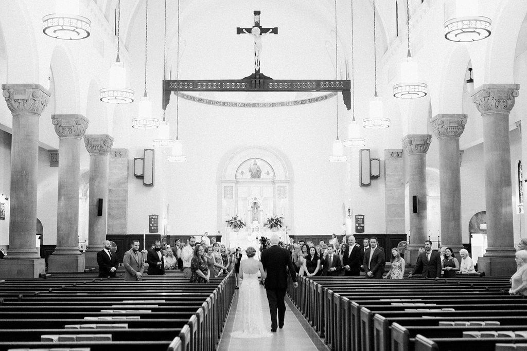 Bride walking down the aisle in black and white at St. Anselm Catholic Church