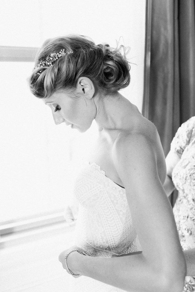 Bride getting into her Rue de Siene wedding dress at the Omni William Penn Hotel