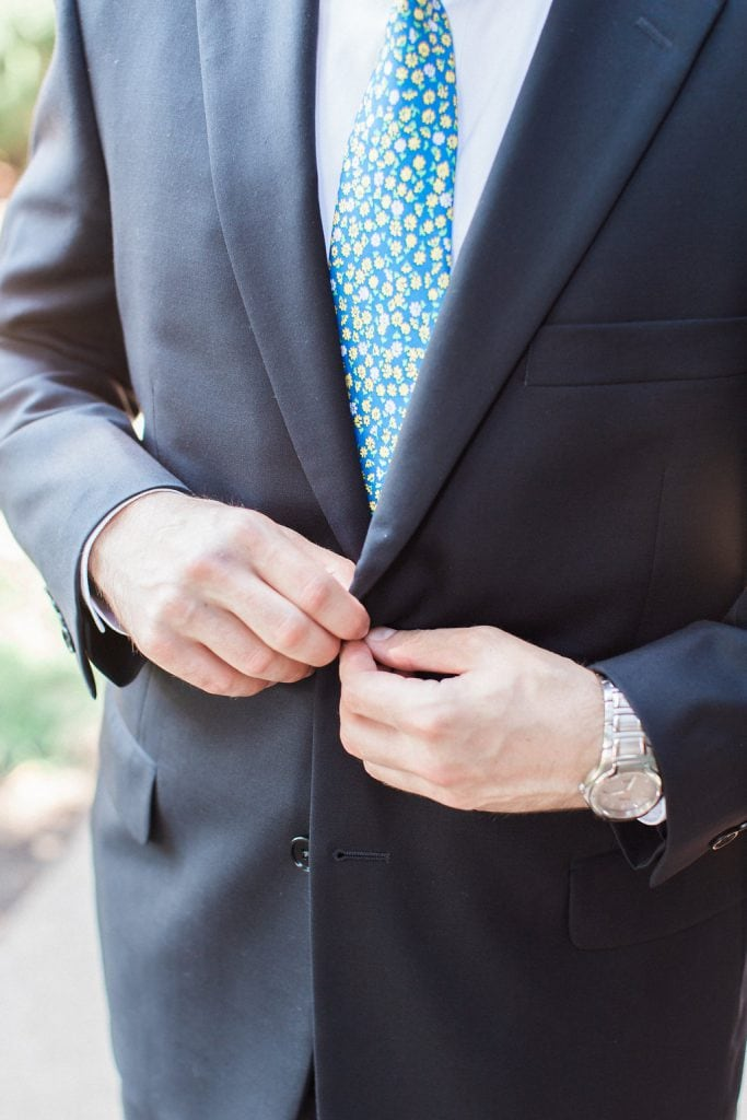 Groom buttoning up his suit jacket