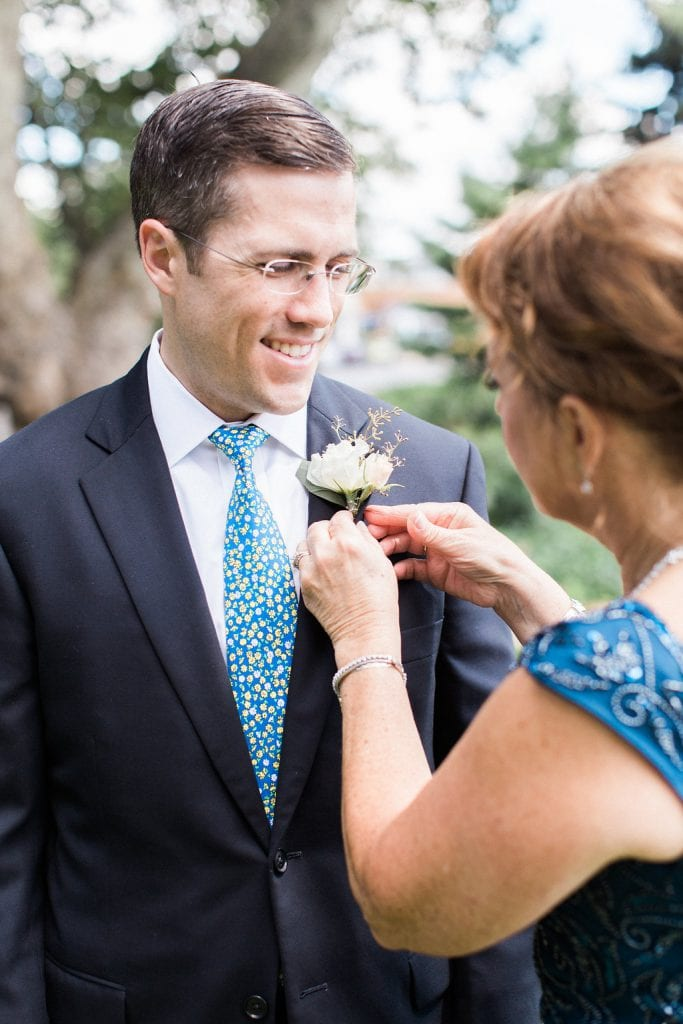 Groom getting boutonnière pinned on by mother at St. Anselm Catholic Church