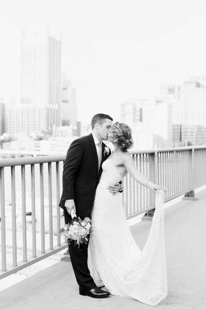 Black and white photograph of the bride and groom on Smithfield Street Bridge overlooking Pittsburgh city skyline