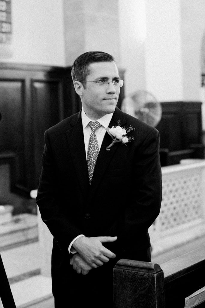 Groom seeing the bride walk down the aisle for the first time in black and white photo