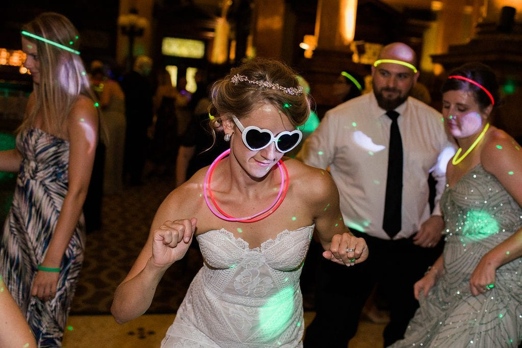 Bride dancing at Grand Concourse Reception with white heart sunglasses on