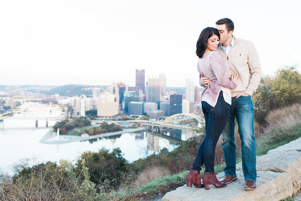 Bride and Groom posing with the Pittsburgh city skyline during engagement photos
