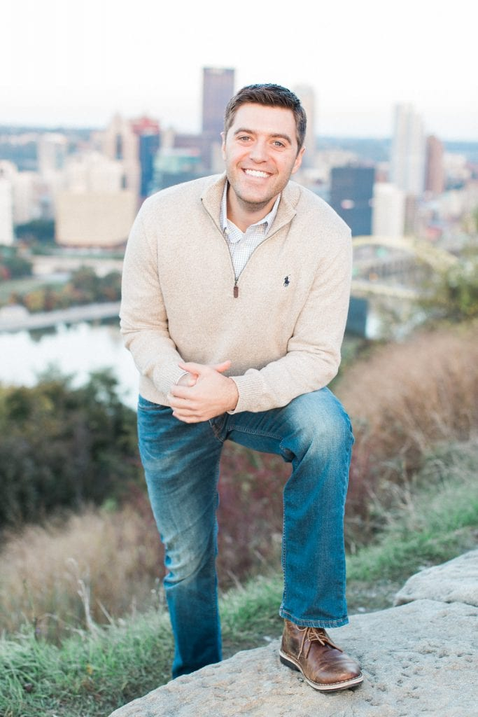 Portrait of groom during engagement photos over looking Pittsburgh Downtown City Skyline