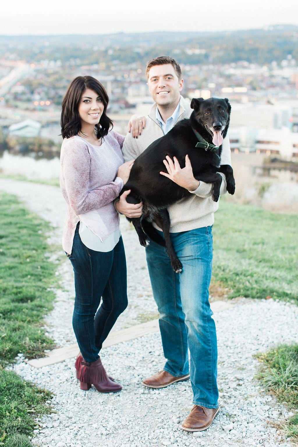 Couple posing with their dog in a photo on top of Mount Washington overlooking Pittsburgh - Mt. Washington & South Side Pittsburgh Engagement Photography