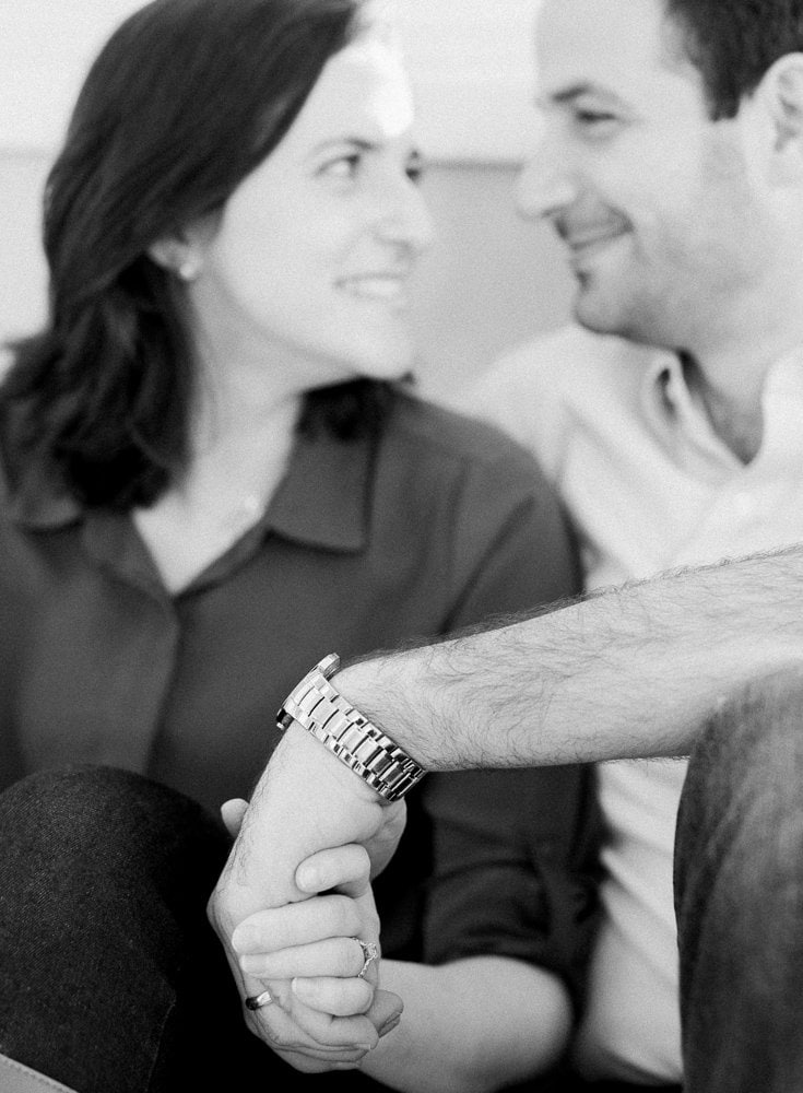 Husband and wife black and white photo during family portraits holding hands