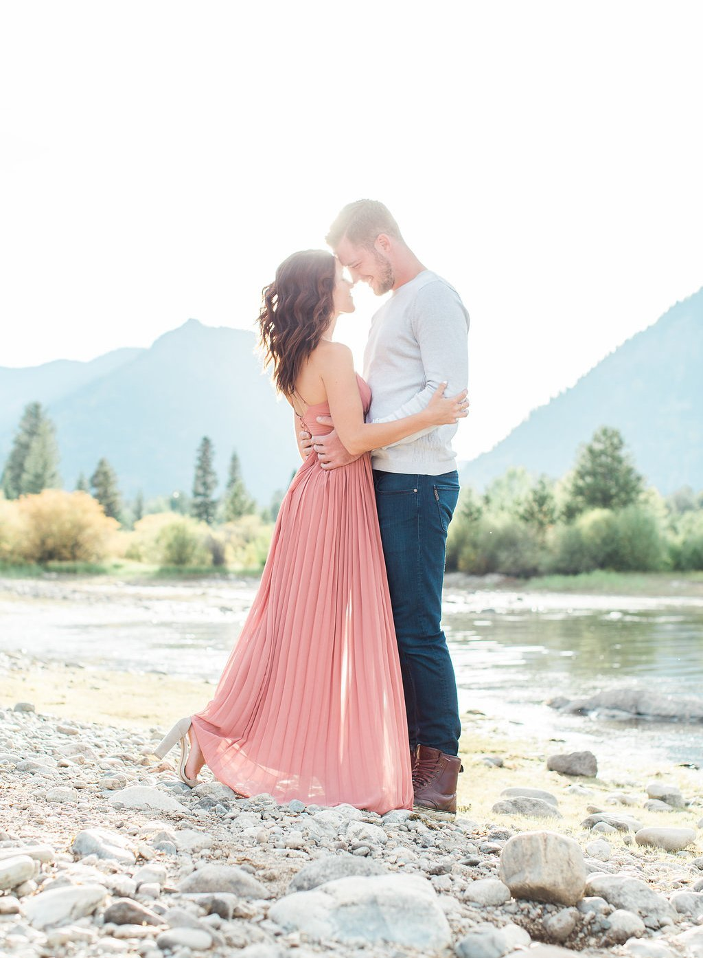 Bride wearing pink and groom near the lake embracing