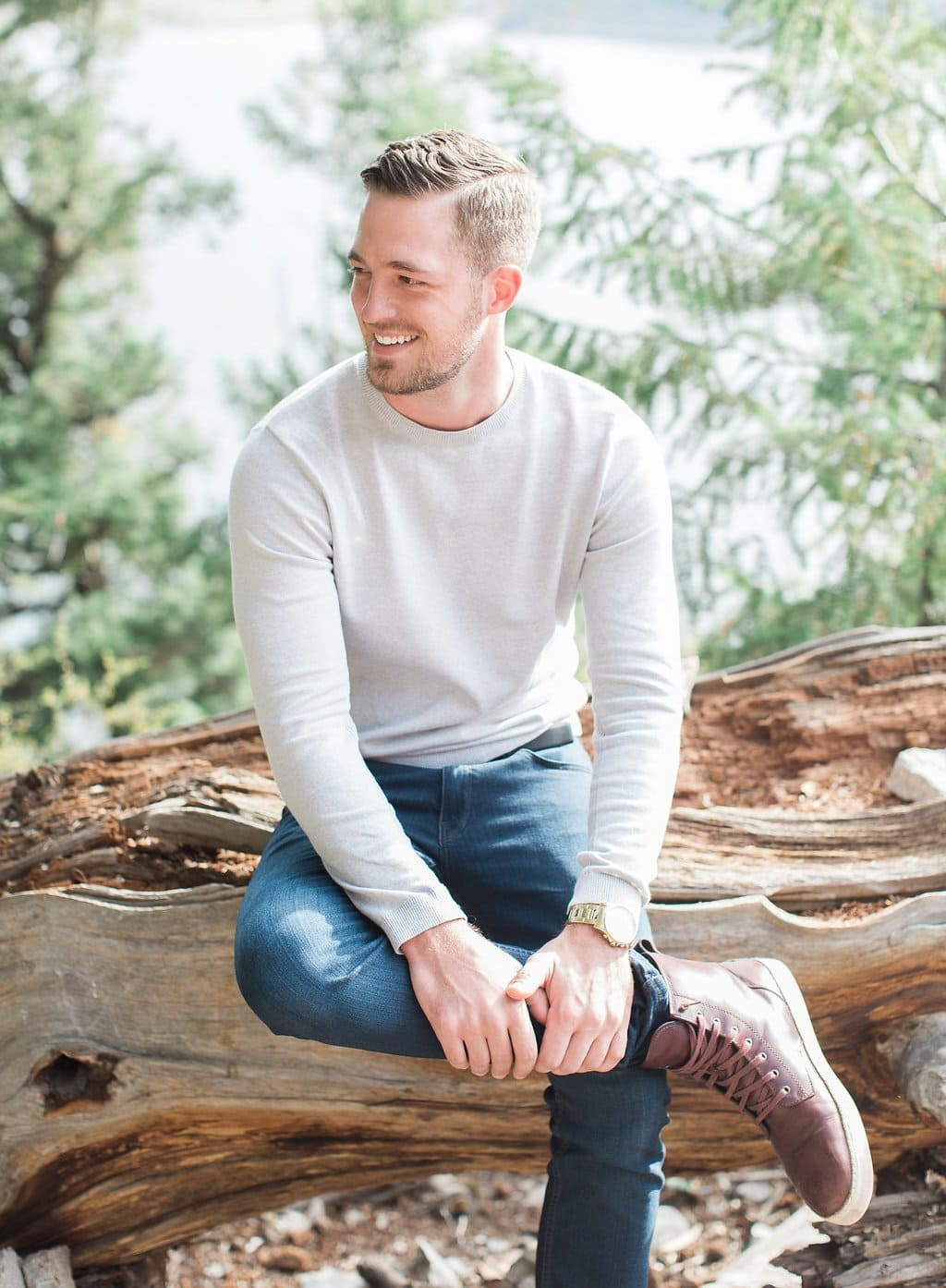 Lake Dillon, Colorado Engagement Photography groom sitting on a log smiling