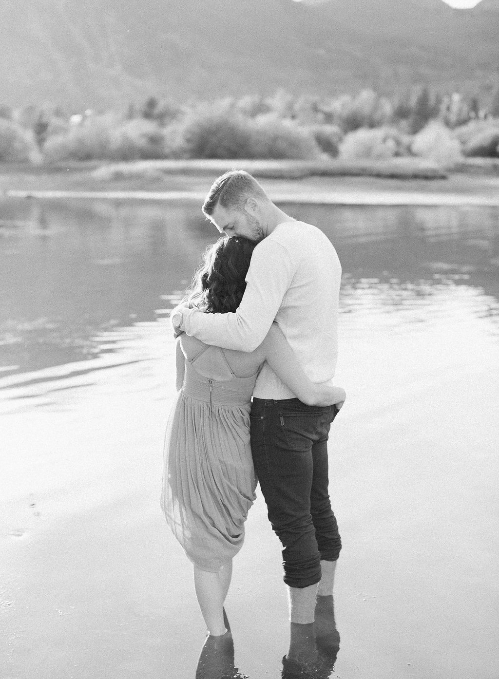 Bride and groom standing in lake kissing black and white