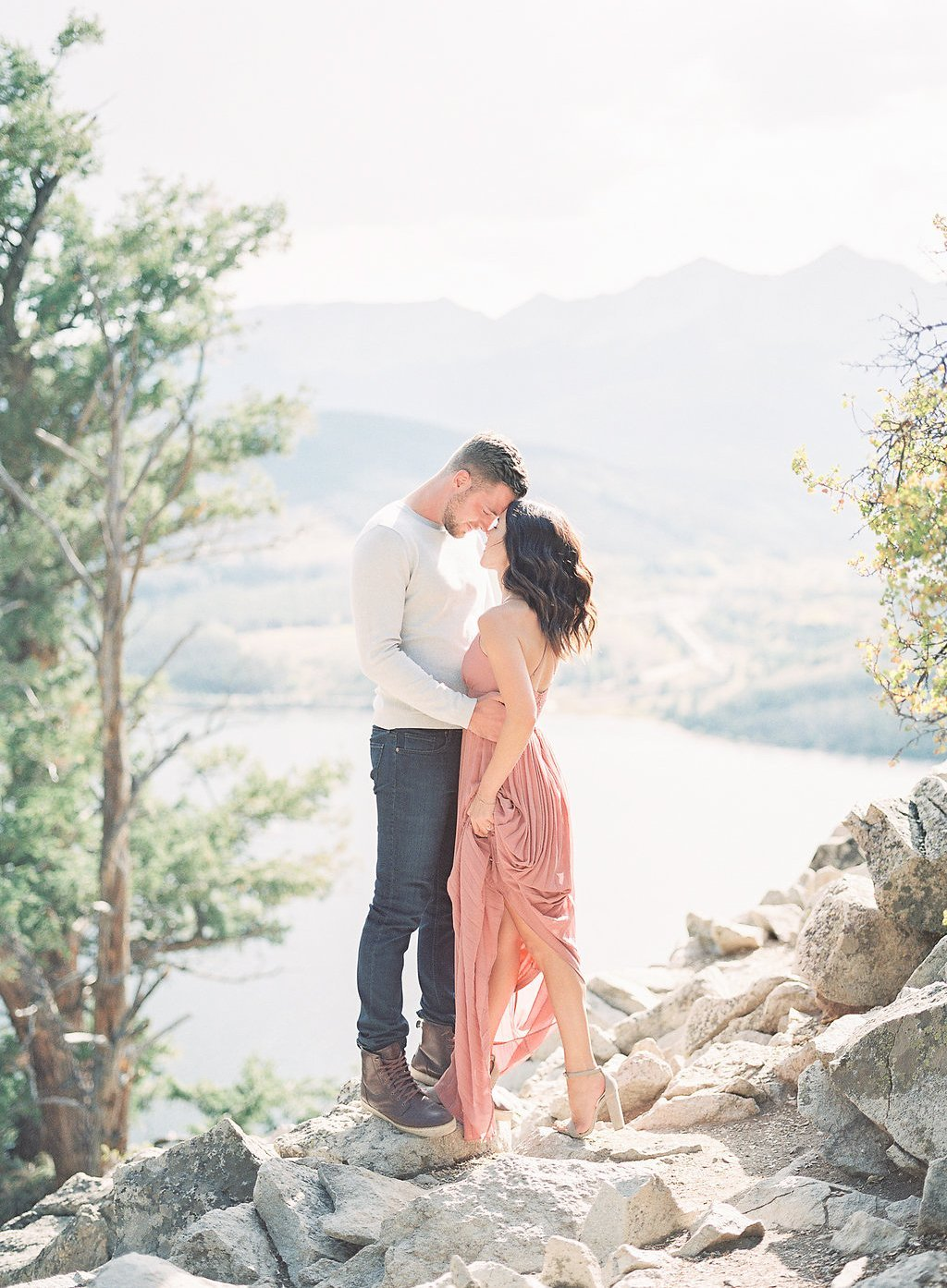 Bride and groom standing on mountain top in the sun