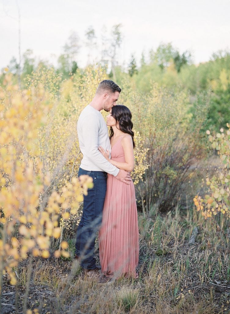 Lake Dillon Colorado Engagement Photography groom and bride embracing amongst the fall leaves