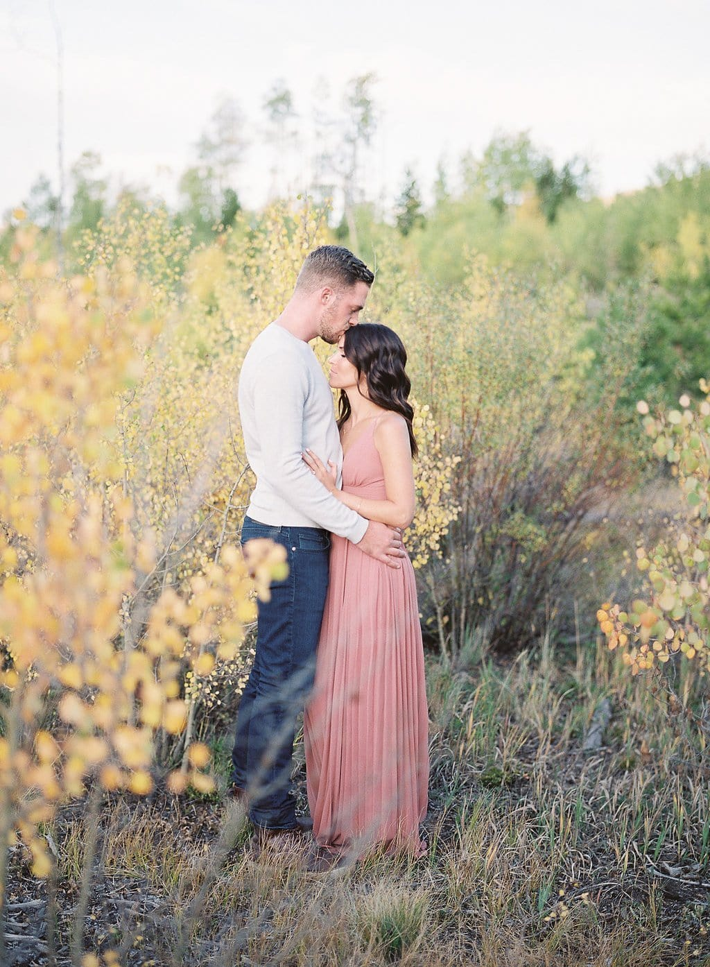 Lake Dillon, Colorado Engagement Photography groom and bride embracing amongst the fall leaves