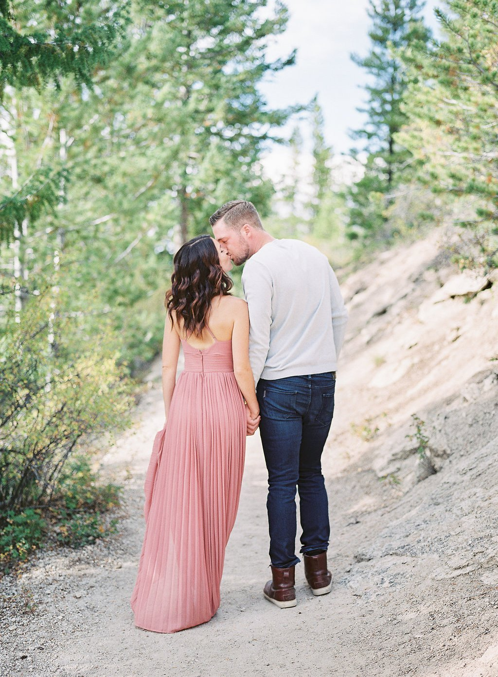 Lake Dillon Colorado Engagement Photography bride and groom walking in the trees kissing