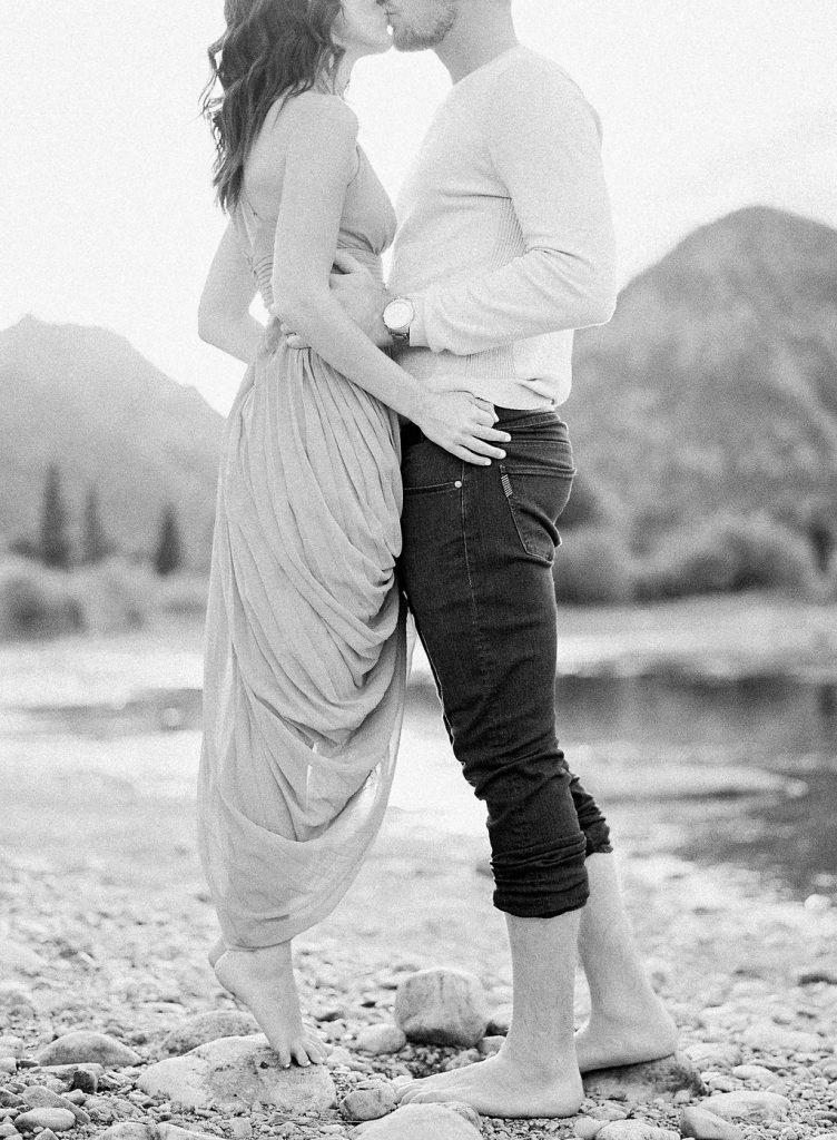 Lake Dillon Colorado Engagement Photography bride standing on her toes to kiss her groom black and white