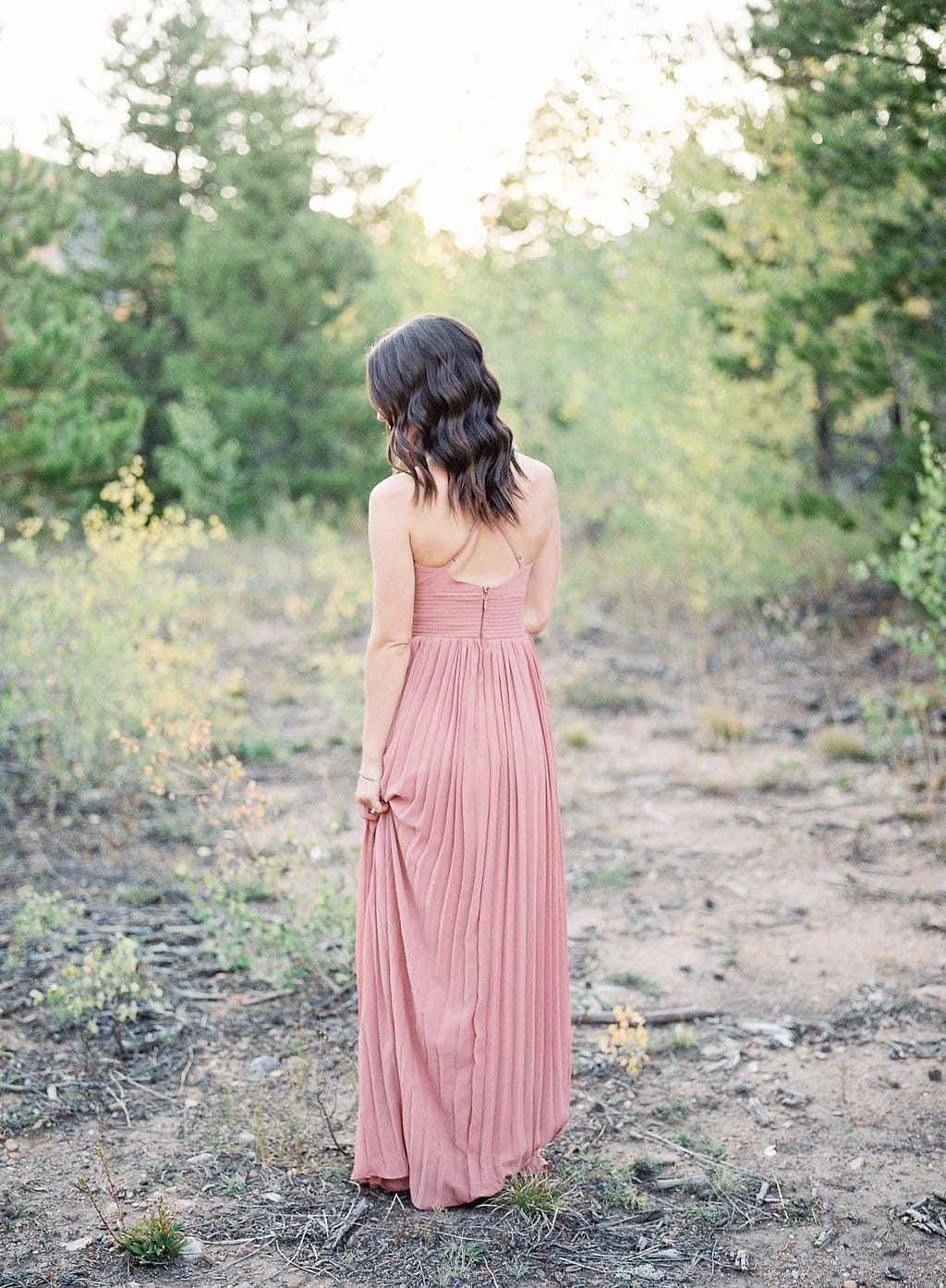 Bride wearing a pink dress and standing in Colorado dessert