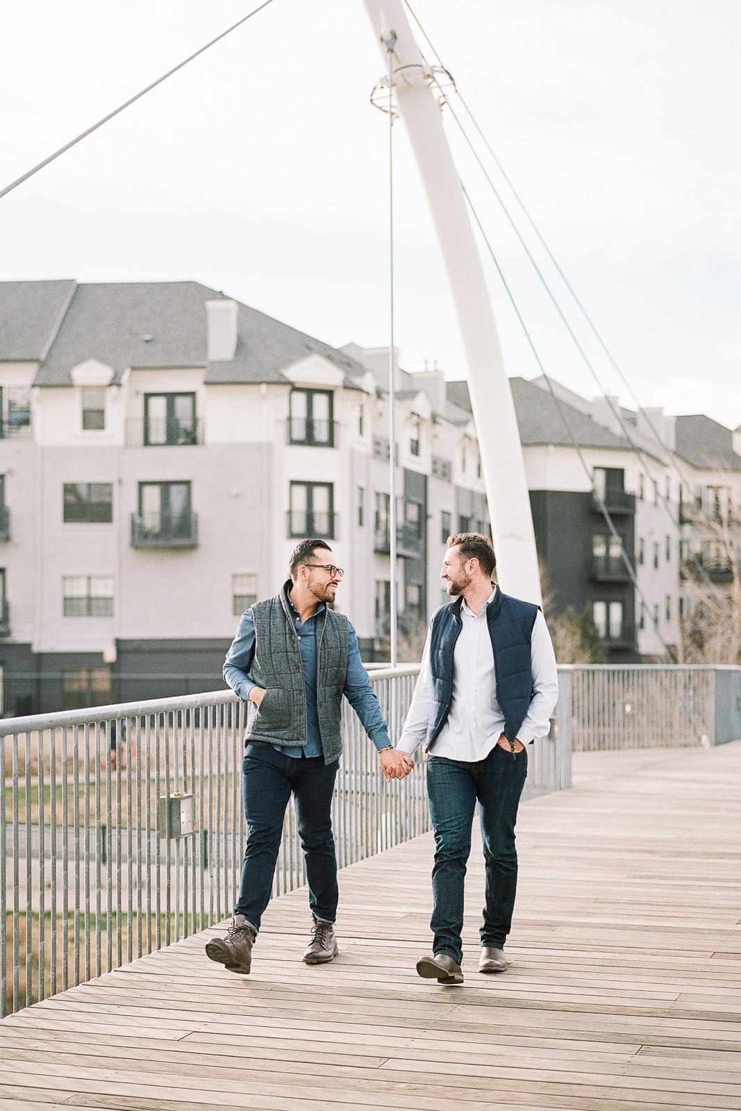 gay couple holding hands walking in downtown denver
