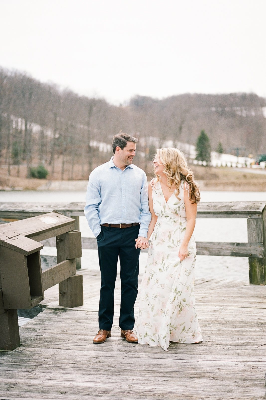 Bride and Groom holding hands and walking on a wooden dock