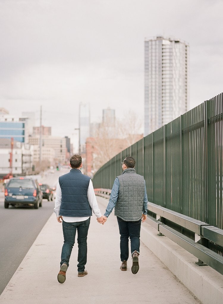 two men holding hands and walking in downtown Denver Colorado