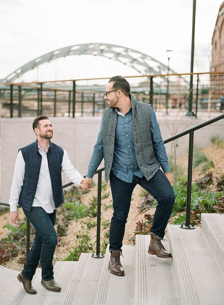Estes Park Engagement Photography Session - gay couple walking up stairs and looking at each other