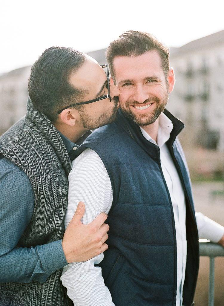 Estes Park Engagement Photography Session - gay couple snuggling on a bridge during portraits