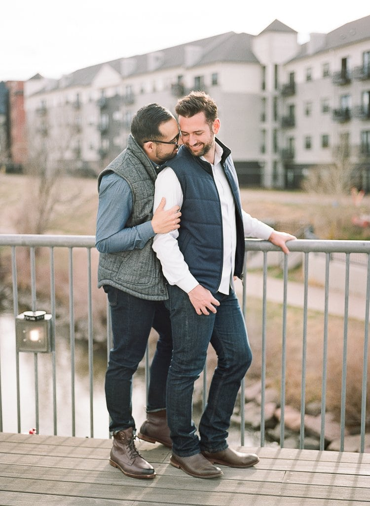 Estes Park Engagement Photography Session - gay men embracing on a bridge in downtown denver