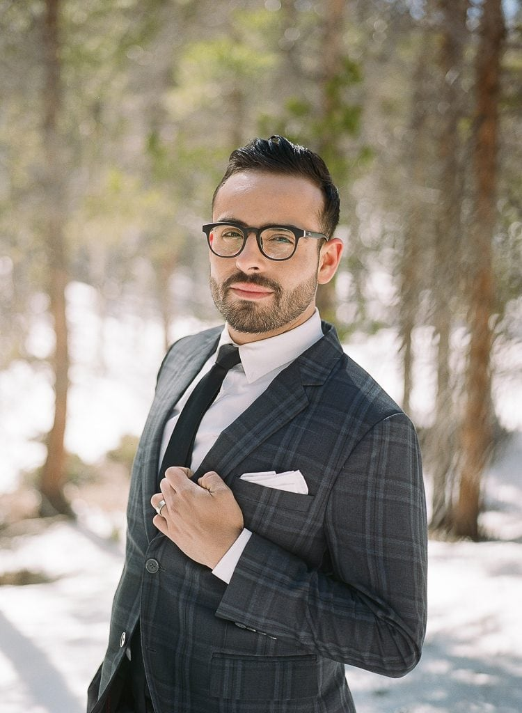 Estes Park Engagement Photography Session - portrait of man with black glasses posing in a suit in the snow