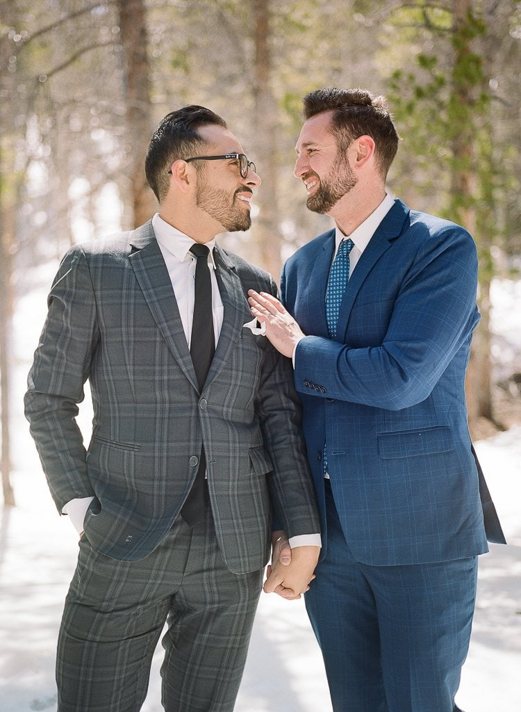 two men in suits holding hands during photo session