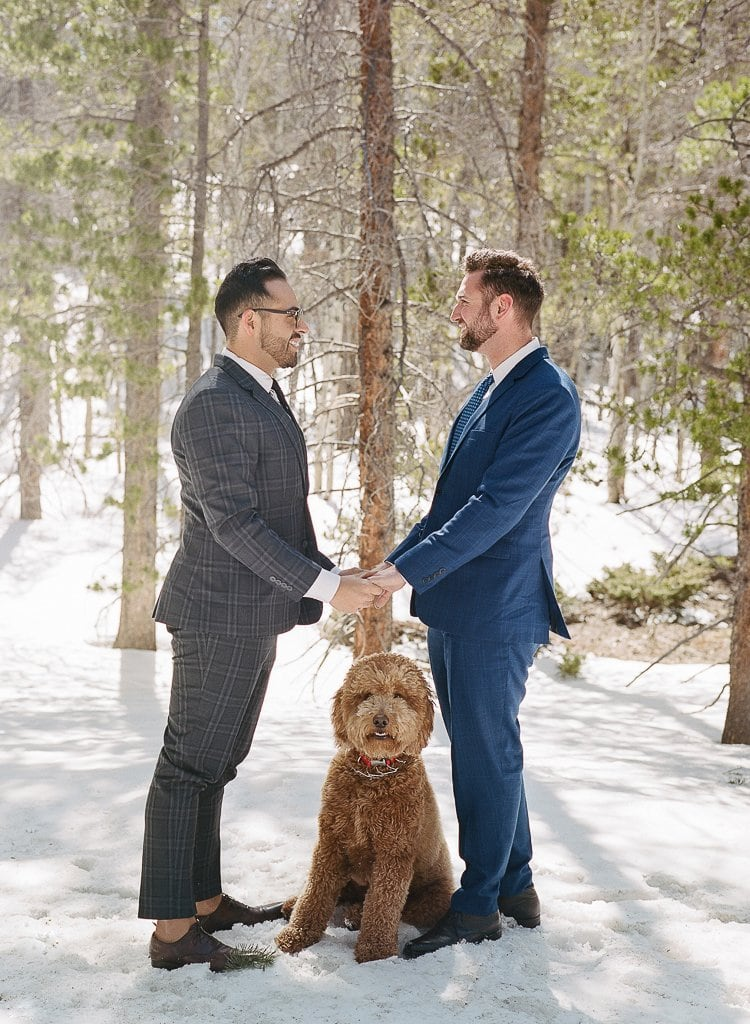 two gay men holding hands in the snow with their dog