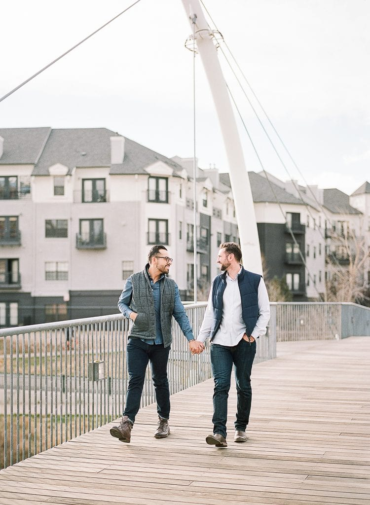 Estes Park Engagement Photography Session - gay couple walking up stairs and looking at each other on a bridge