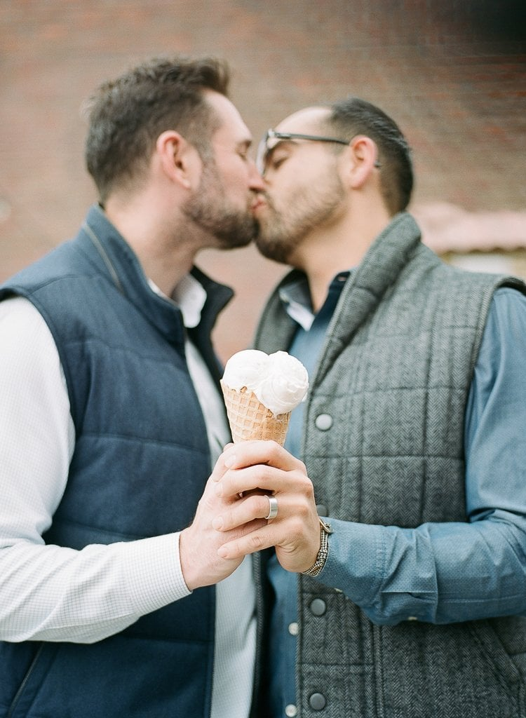 male gay couple kissing and sharing ice cream cone
