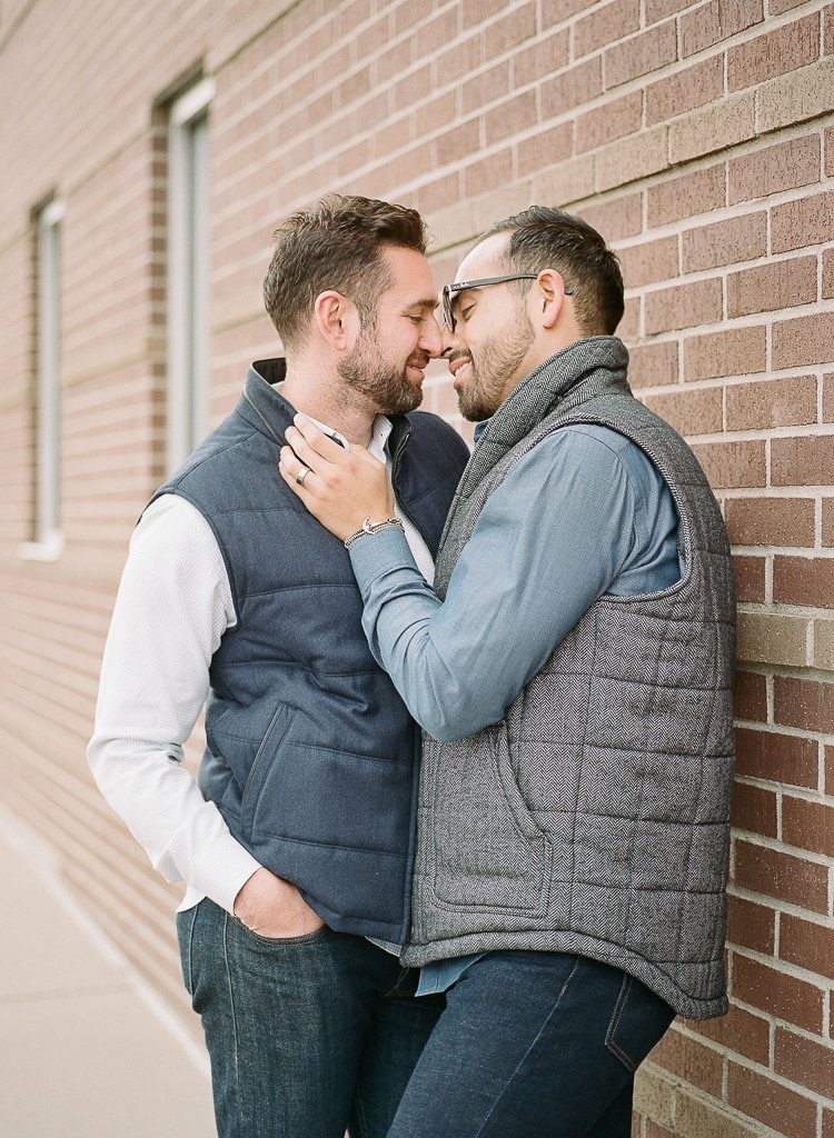 two gay men embracing leaning against a brick wall in downtown Denver Colorado
