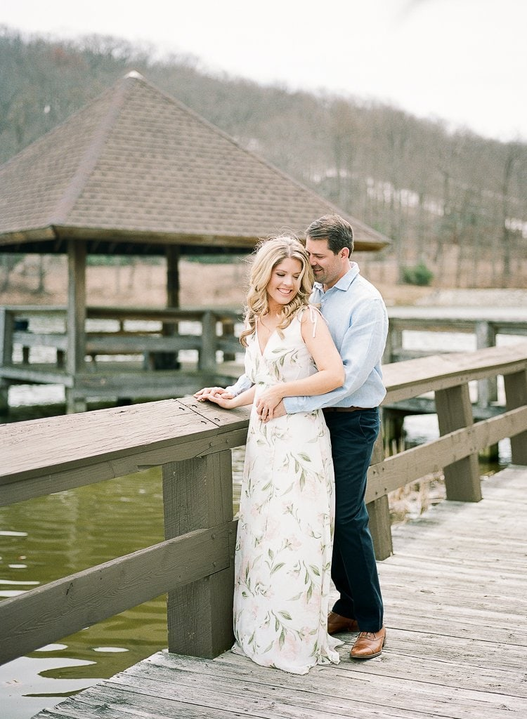 bride and groom standing near a dock laughing