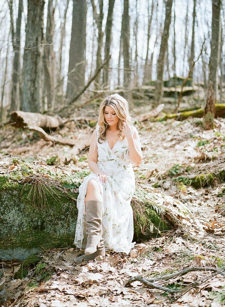 bride sitting on a rock in the woods