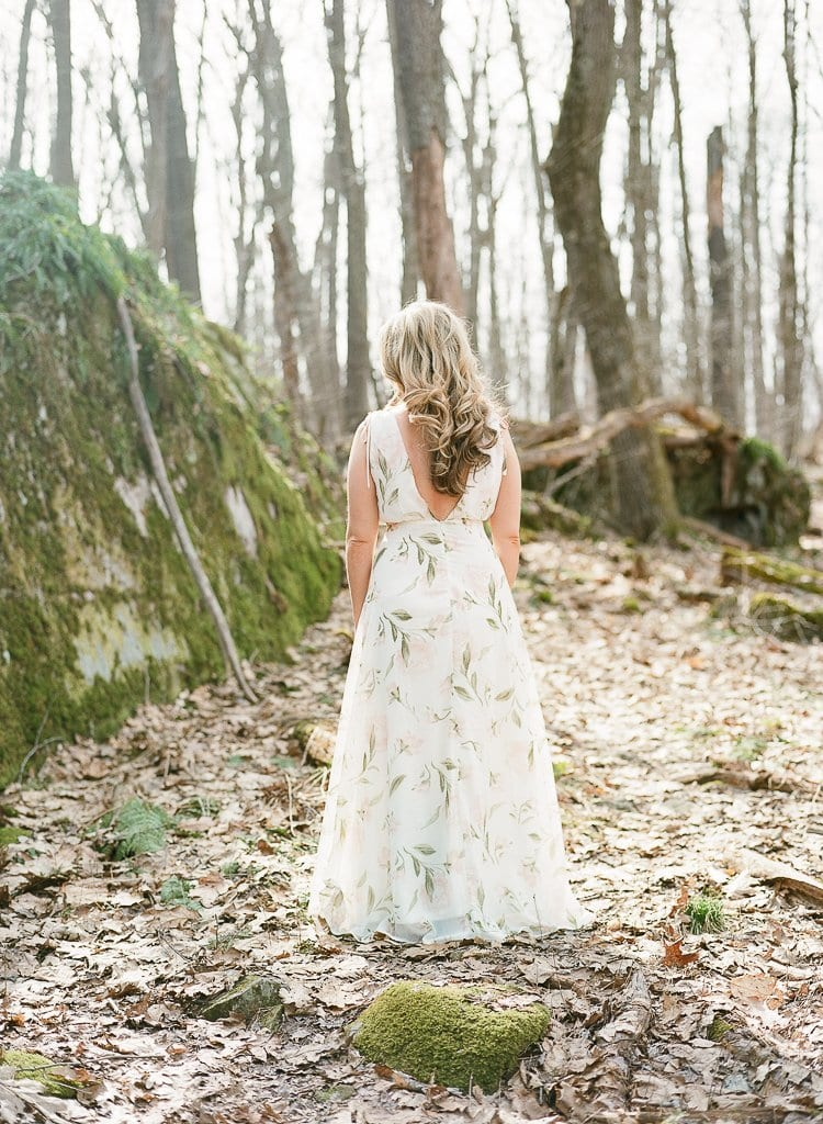 bride standing in the woods near moss covered rocks