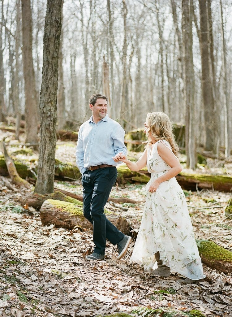 bride and groom walking in the woods holding hands