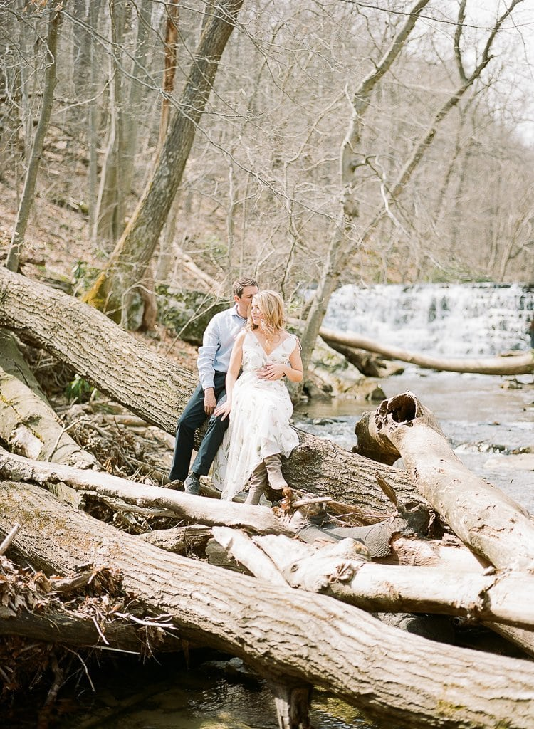 bride and groom sitting on a log near the stream