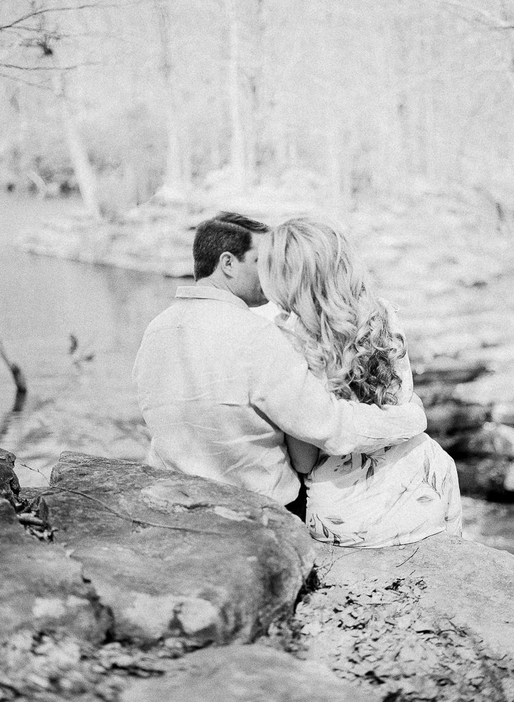 Seven Springs Engagement Photography - black and white photo of bride and groom kissing over a waterfall