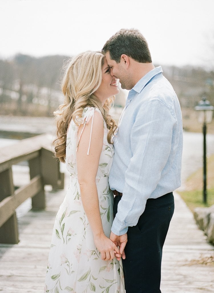 Seven Springs Engagement Photography - bride and groom snuggling and holding hands on a dock