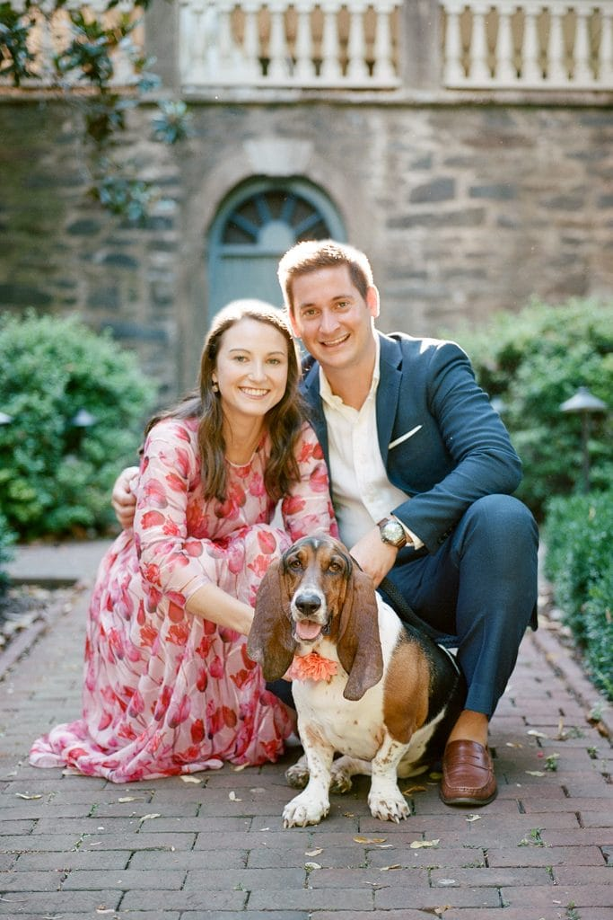Couple posing for engagement photos at the Carlyle House with their dog in Old Town Alexandria