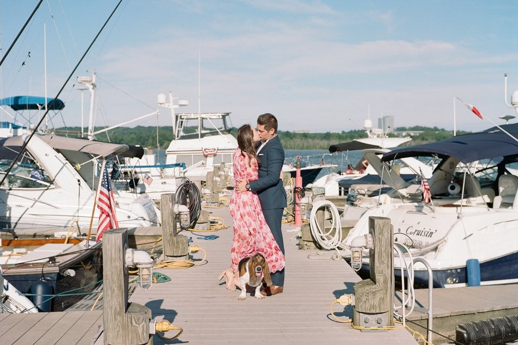 Couple kissing while walking their hound dog on the docks on Old Town Harbor in Virginia - Engagement Photography Session in Old Town Alexandria, Virginia