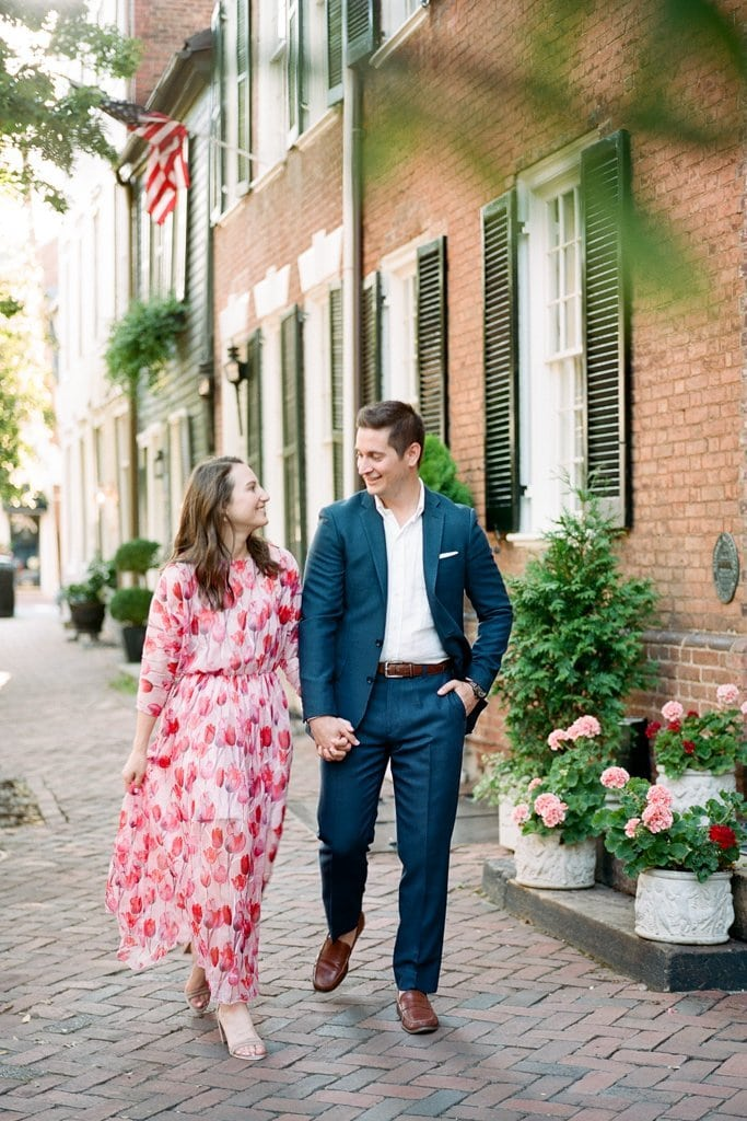 couple walking down the street holding hands in Old Town Alexandria Virginia during engagement session