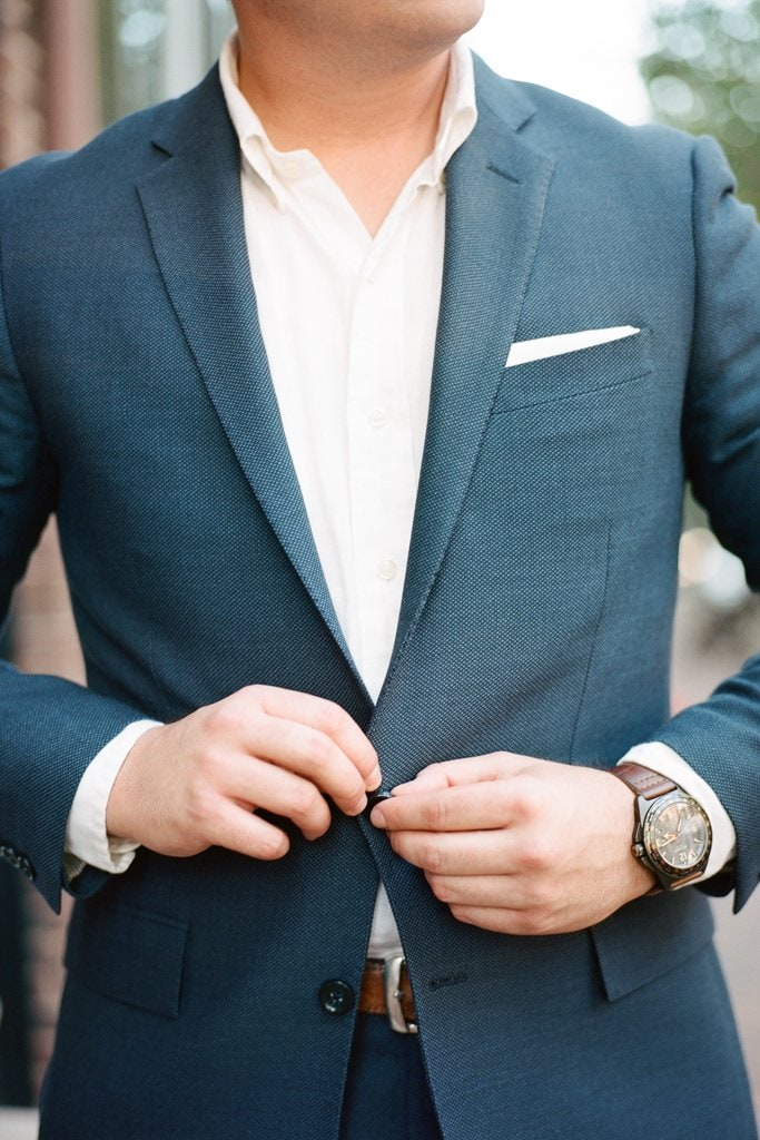 groom buttoning up his blue suit during engagement photos