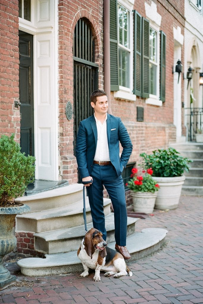 Young man standing on a stoop in a suit with his hound dog