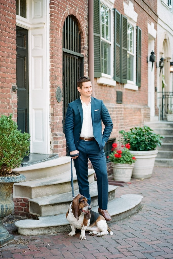 Young man standing on a stoop in a suit with his hound dog -  Engagement Photography Session in Old Town Alexandria, Virginia